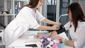 Docteur et prise de la pression artérielle patiente vers le haut - de patient féminin banque de vidéos