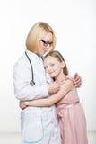 Docteur et une patiente de sourire de fille D'isolement sur le fond blanc Photos libres de droits