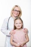 Docteur et une patiente de sourire de fille D'isolement sur le fond blanc Photographie stock