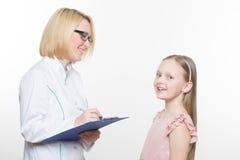 Docteur et une patiente de sourire de fille Sur le fond blanc Image stock