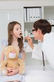 Docteur examinant la bouche de petite fille photos libres de droits