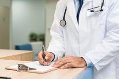 Docteur examinant le rapport médical image stock