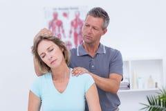 Docteur examinant son cou patient Image stock