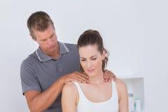 Docteur examinant son cou patient Images stock