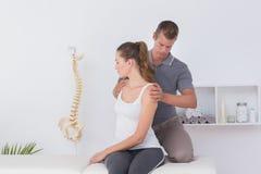 Docteur examinant son cou patient Photographie stock libre de droits
