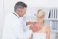 Docteur examinant son dos de patient Image stock