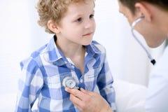 Docteur examinant un patient d'enfant par le stéthoscope Images stock