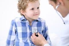Docteur examinant un patient d'enfant par le stéthoscope Image libre de droits