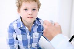 Docteur examinant un patient d'enfant par le stéthoscope Photo libre de droits