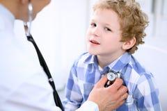 Docteur examinant un patient d'enfant par le stéthoscope Image stock