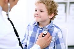 Docteur examinant un patient d'enfant par le stéthoscope Photos stock
