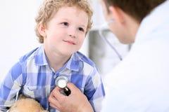 Docteur examinant un patient d'enfant par le stéthoscope Photo stock