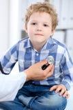 Docteur examinant un patient d'enfant par le stéthoscope Photographie stock libre de droits