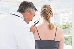 Docteur examinant une tache à son patient Photos stock