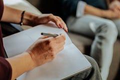 Docteur expérimenté focalisé de la psychologie notant des notes au sujet des problèmes images libres de droits