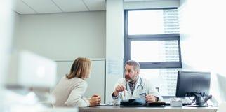 Docteur expliquant le diagnostic au patient féminin images libres de droits