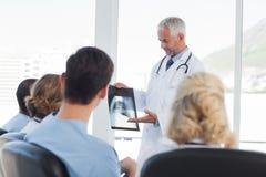 Docteur expliquant le rayon X à son équipe Photo libre de droits