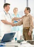 Docteur félicitant le patient aîné sur la reprise Image stock