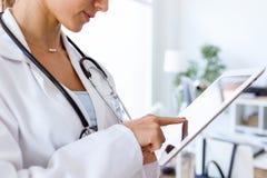 Docteur féminin à l'aide de son comprimé numérique dans le bureau Photographie stock