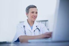 Docteur féminin à l'aide de son ordinateur portable Photos stock