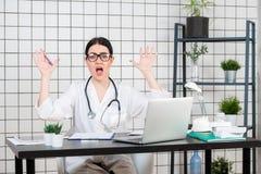 Docteur féminin étonné regardant l'ordinateur portable Médecin à son bureau fonctionnant Actualités inattendues ou résultats d'es image stock
