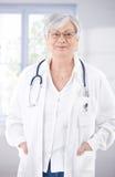 Docteur féminin aîné souriant au couloir d'hôpital Photos stock