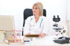 Docteur féminin aîné travaillant au bureau Images stock
