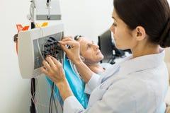 Docteur féminin accordant l'électro-encéphalographe moderne Photographie stock