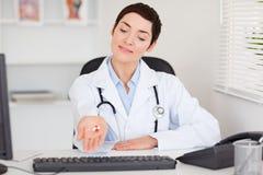 Docteur féminin affichant des pillules Photo stock
