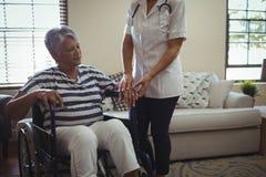 Docteur féminin agissant l'un sur l'autre avec la femme supérieure sur le fauteuil roulant Photo stock