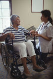 Docteur féminin agissant l'un sur l'autre avec la femme supérieure sur le fauteuil roulant Photos stock