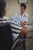 Docteur féminin agissant l'un sur l'autre avec la femme supérieure sur le fauteuil roulant Images libres de droits