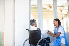 Docteur féminin agissant l'un sur l'autre avec la femme supérieure sur le fauteuil roulant Photographie stock libre de droits