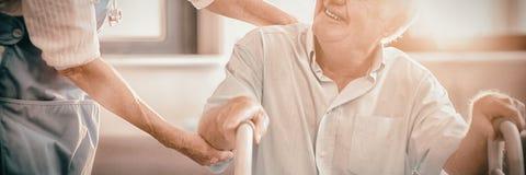 Docteur féminin aidant l'homme supérieur à marcher avec le marcheur photos stock