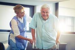 Docteur féminin aidant l'homme supérieur à marcher avec le marcheur photo stock