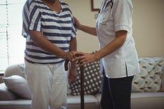 Docteur féminin aidant la femme supérieure à marcher avec le bâton de marche Image libre de droits