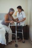 Docteur féminin aidant la femme supérieure à marcher avec le marcheur images stock