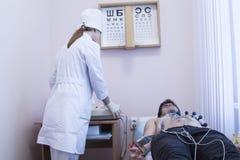 Docteur féminin analysant l'électrocardiogramme d'ECG du patient à dans l'hôpital Photographie stock