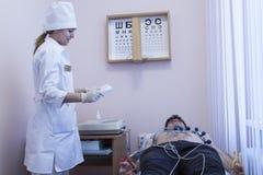 Docteur féminin analysant l'électrocardiogramme d'ECG du patient à dans l'hôpital Photographie stock libre de droits