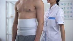 Docteur féminin appliquant de retour le patient masculin d'enveloppe pour diminuer la blessure hypoxique de tissu banque de vidéos