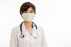 Docteur féminin asiatique avec le masque chirurgical regardant l'appareil-photo Images stock