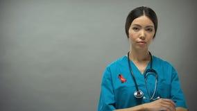Docteur féminin asiatique avec le ruban rouge, signe international de conscience de SIDA d'HIV banque de vidéos