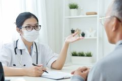 Docteur féminin asiatique parlant au patient d'homme supérieur Photo libre de droits