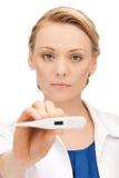 Docteur féminin attirant avec le thermomètre Images stock