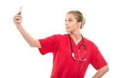 Docteur féminin attirant prenant le selfie avec le smartphone Photo libre de droits