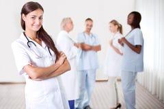 Docteur féminin avec des collègues à l'arrière-plan Photographie stock