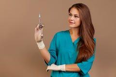 Docteur féminin avec la fiole et la seringue dans l'hôpital Jour de vaccination Fond beige photographie stock libre de droits