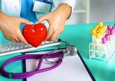 Docteur féminin avec le coeur de fixation de stéthoscope Docteur et patient s'asseyant à l'arrière-plan Photos libres de droits