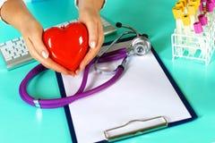 Docteur féminin avec le coeur de fixation de stéthoscope Docteur et patient s'asseyant à l'arrière-plan Images libres de droits