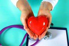 Docteur féminin avec le coeur de fixation de stéthoscope Docteur et patient s'asseyant à l'arrière-plan Photo stock